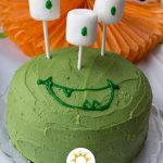 Green monster birthday cake with marshmallow eyes on a decorated table (with title overlay)