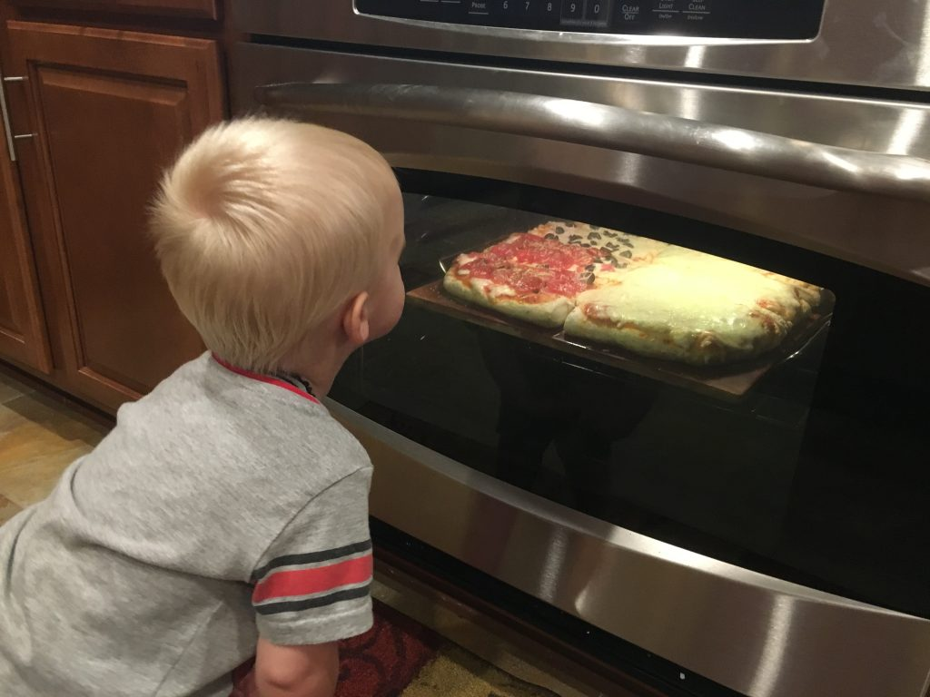 Young boy watching homemade pizza bake in the oven