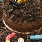 Construction truck dirt cake with plastic toy and gummy worms (with title and description overlay)