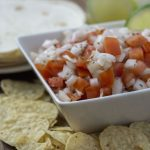 Pico de Gallo in a square bowl with chips in front of the bowl and tortillas behind it all on a wooden surface