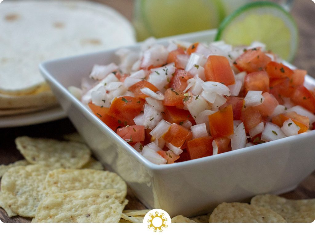 Pico de Gallo in a square bowl with chips in front of the bowl and tortillas behind it all on a wooden surface (with logo overlay)