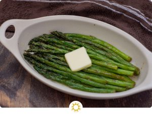 Roasted Asparagus in an oval bowl with a pat of butter on top (with logo overlay)