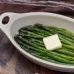 Roasted Asparagus in an oval bowl with a pat of butter on top (with title overlay)