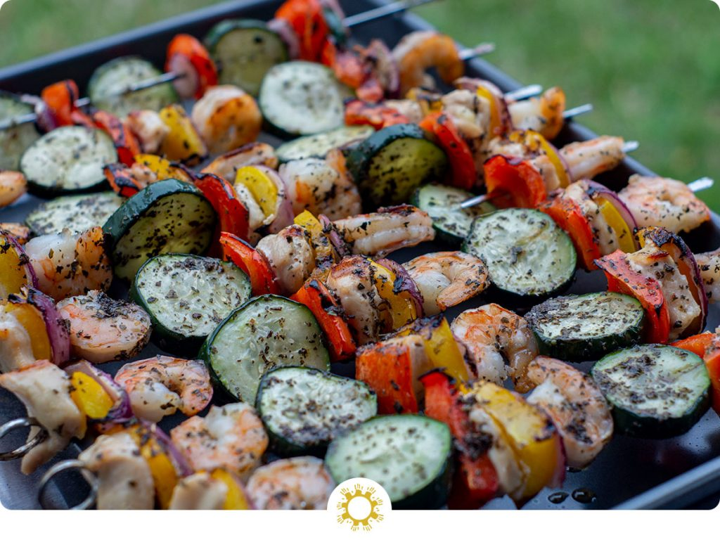 Summer Basil Chicken and Shrimp Kabobs on a metal sheet pan with grass in the background (with logo overlay)