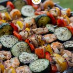 Summer Basil Chicken and Shrimp Kabobs on a metal sheet pan with grass in the background (with title overlay)