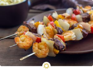 Steak and Shrimp Kabobs on a brown plate with a bowl of potato salad in the background (with logo overlay)