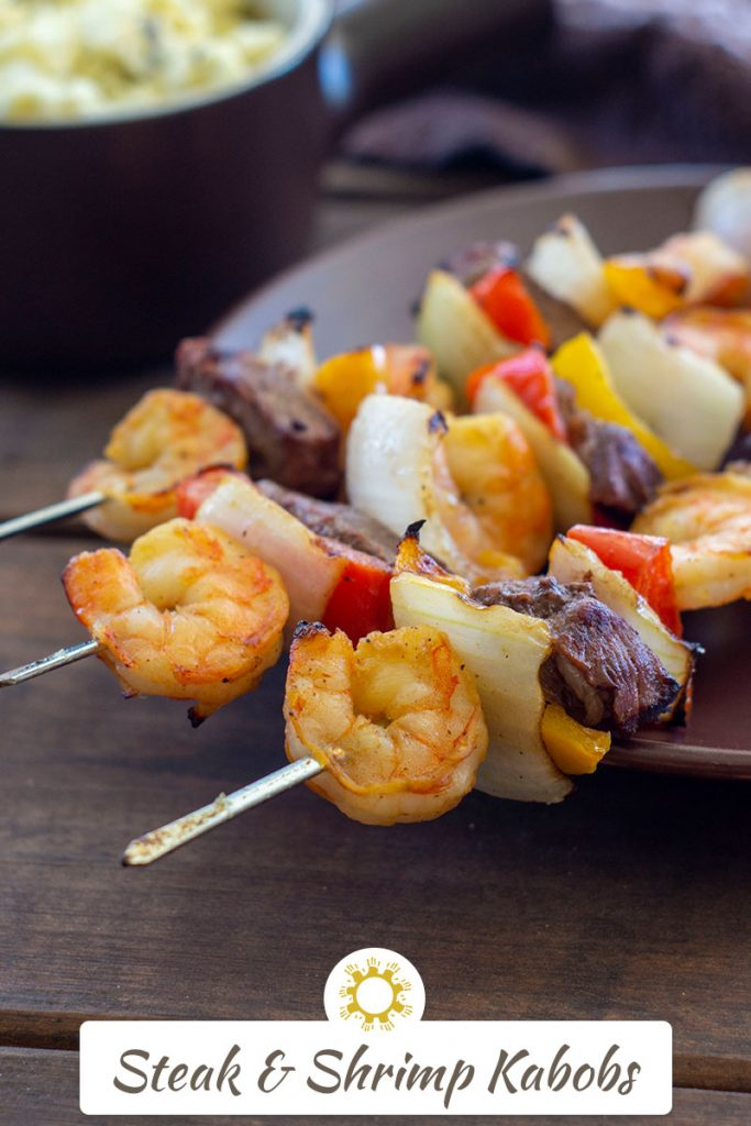 Steak and Shrimp Kabobs on a brown plate with a bowl of potato salad in the background (with title overlay)