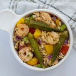 Shrimp and okra bowl recipe in a white bowl with a towel next to it (with title overlay)