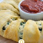 Close up of cheesy chicken and spinach stromboli ring from the side with a white ramekin of marinara sauce in the center on a bamboo cutting board over a white and grey marble surface (vertical with title overlay)