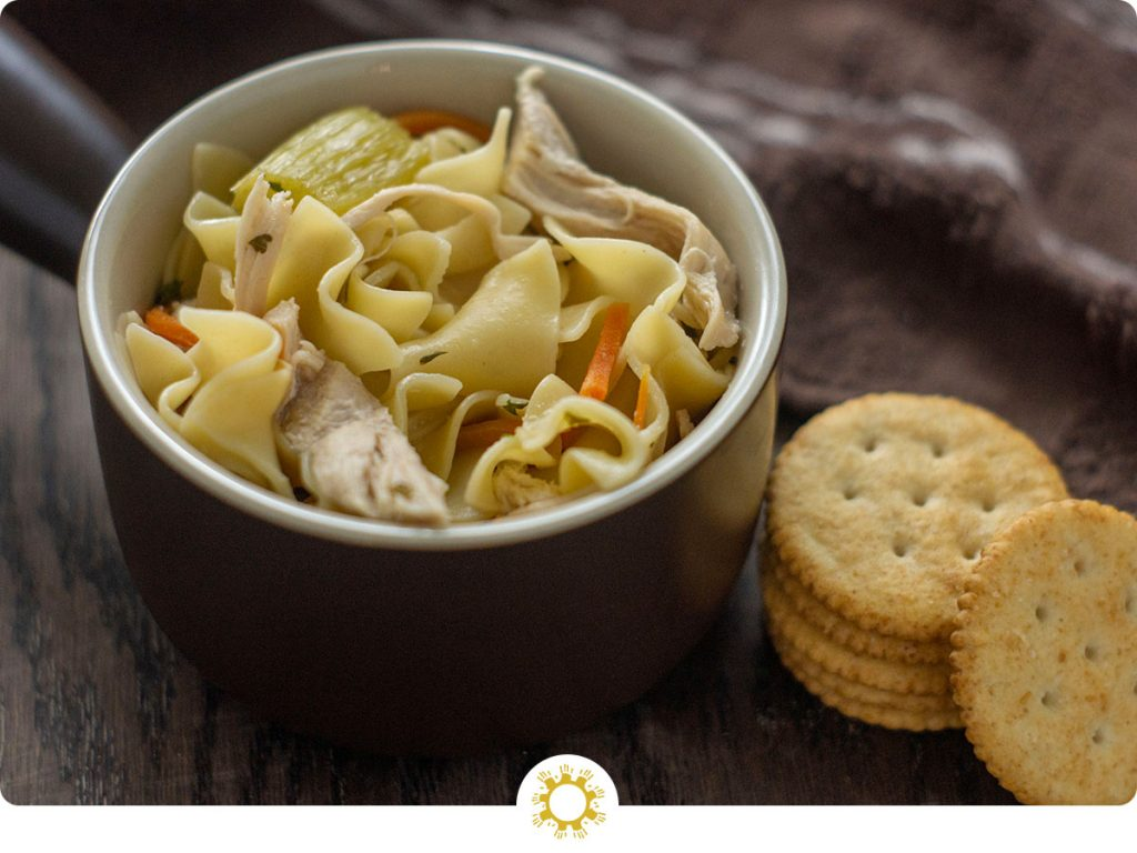 One Pot Chicken Noodle Soup in a round brown bowl next to crackers with a brown towel behind all on a wooden surface (with logo overlay)
