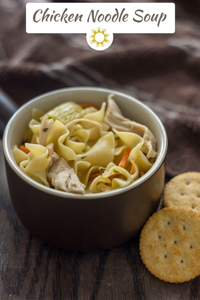 One Pot Chicken Noodle Soup in a round brown bowl next to crackers with a brown towel behind all on a wooden surface (vertical with title overlay)
