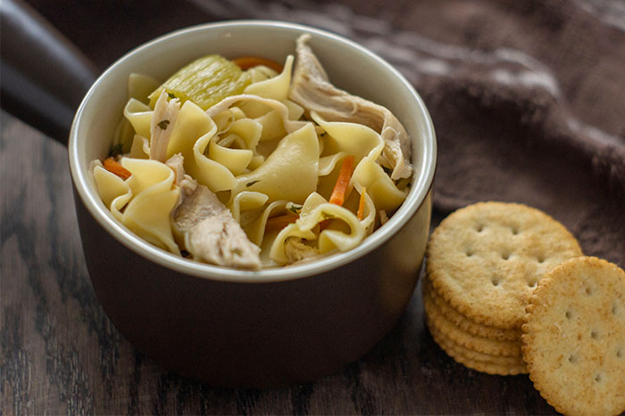 One Pot Chicken Noodle Soup in a round brown bowl next to crackers with a brown towel behind all on a wooden surface