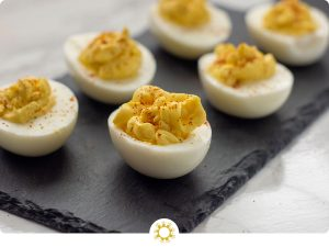 Super Easy Classic Deviled Eggs garnished with paprika on a slate serving plate on top of a white and grey marble surface (with logo overlay)