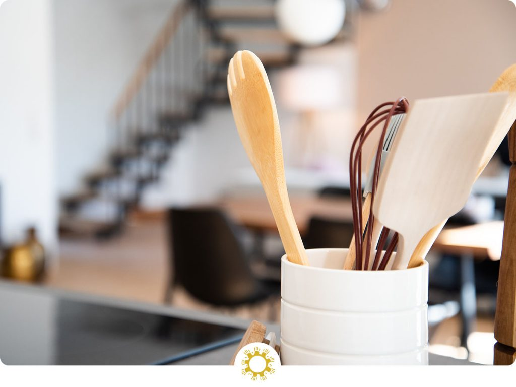 Shallow focus of cooking utensils in a white canister in a kitchen (with logo overlay)
