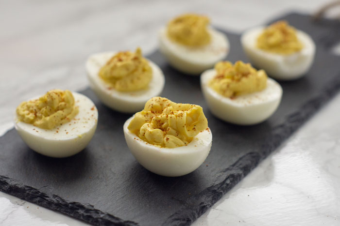 Super Easy Classic Deviled Eggs garnished with paprika on a slate serving plate on top of a white and grey marble surface