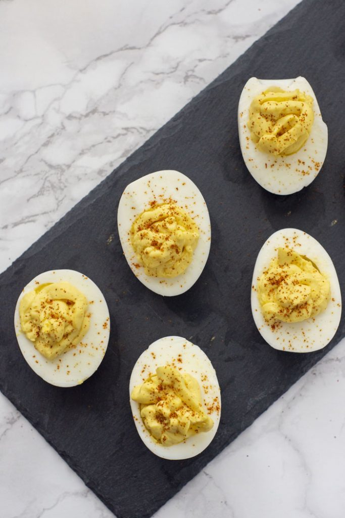 Overhead view of Super Easy Classic Deviled Eggs garnished with paprika on a slate serving plate on top of a white and grey marble surface