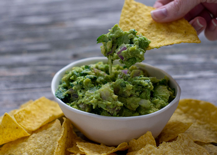 Woman's hand pulling a tortilla chip from a white bowl of guacamole surrounded by tortilla chips on a wooden surface
