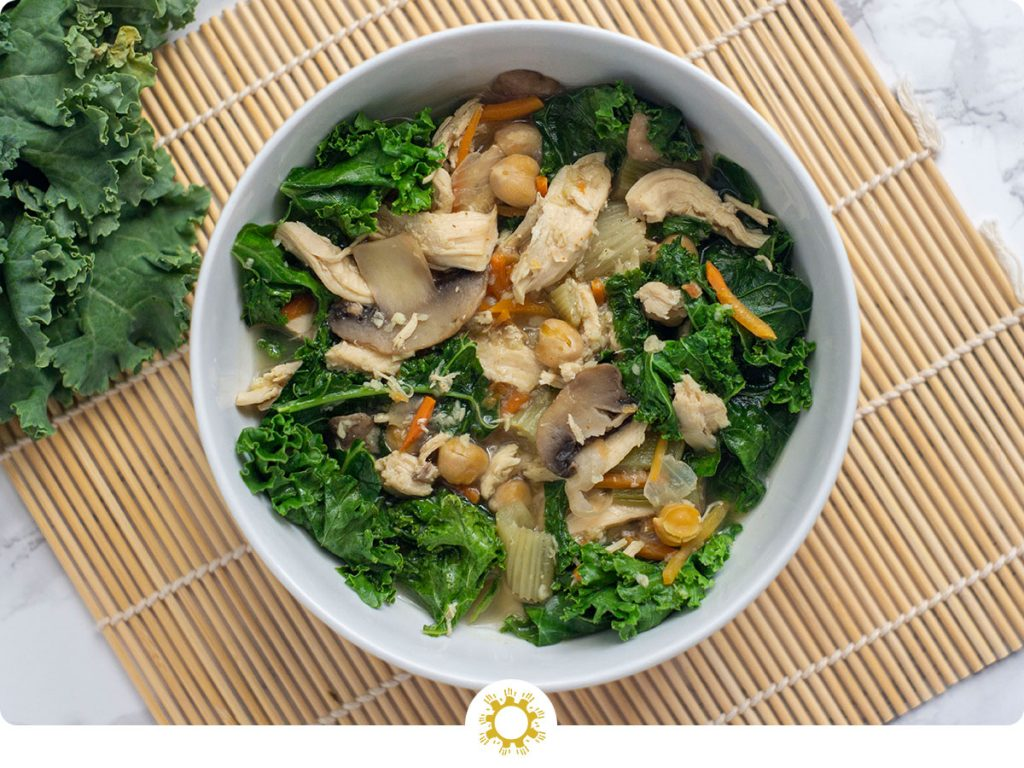 Immunity Soup: Cooked broth with vegetables, chicken, chickpeas, and kale in a round white dish on a bamboo mat next to raw kale on a white and grey marble surface (with logo overlay)