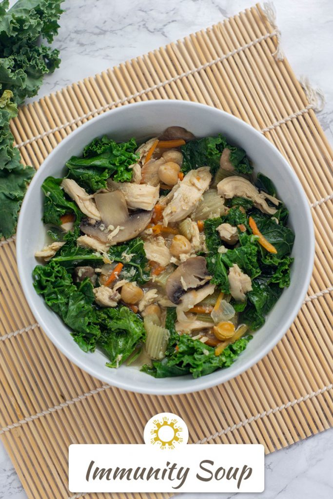 Immunity Soup: Cooked broth with vegetables, chicken, chickpeas, and kale in a round white dish on a bamboo mat next to raw kale on a white and grey marble surface (vertical with title overlay)
