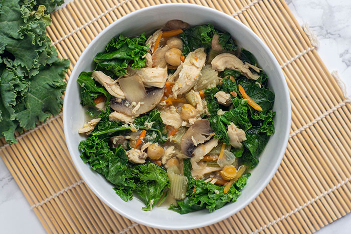 Immunity Soup: Cooked broth with vegetables, chicken, chickpeas, and kale in a round white dish on a bamboo mat next to raw kale on a white and grey marble surface