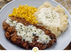 Creamy Buttermilk Chicken-Fried Chicken covered with white gravy next to mashed potatoes with gravy and steamed corn on a round white plate (with logo overlay)