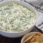 Round white bowl full of spinach artichoke dip with a small round white bowl of crackers in front and a white and grey towel behind all on a wooden surface (vertical with title overlay)