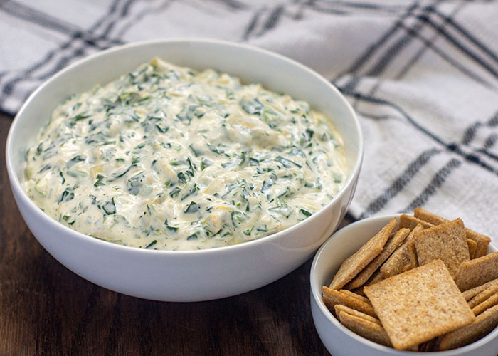 Round white bowl full of spinach artichoke dip with a small round white bowl of crackers in front and a white and grey towel behind all on a wooden surface