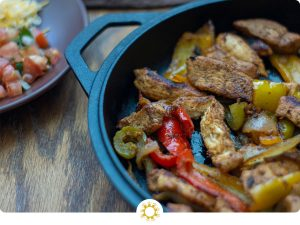 Chicken fajita meat and veggies in a cast-iron pan (with logo overlay)