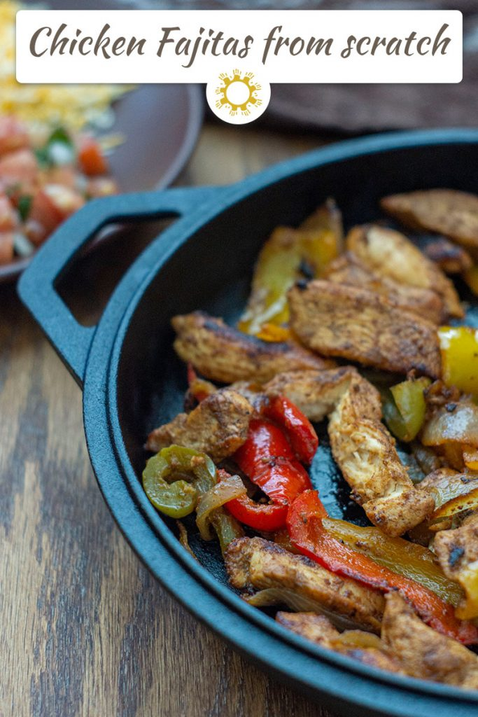 Chicken fajita meat and veggies in a cast-iron pan (with title overlay)