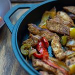 Chicken fajita meat and veggies in a cast-iron pan