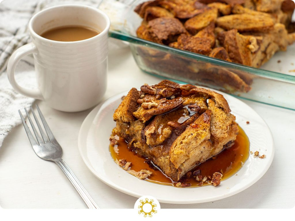 French Toast Casserole topped with chopped pecans and maple syrup on a round white plate next to a fork and a white cup of coffee with the dish of remaining casserole and a white towel in the background all on a white surface (with logo overlay)