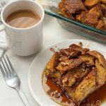 French Toast Casserole topped with chopped pecans and maple syrup on a round white plate next to a fork and a white cup of coffee with the dish of remaining casserole and a white towel in the background all on a white surface (vertical with title overlay)