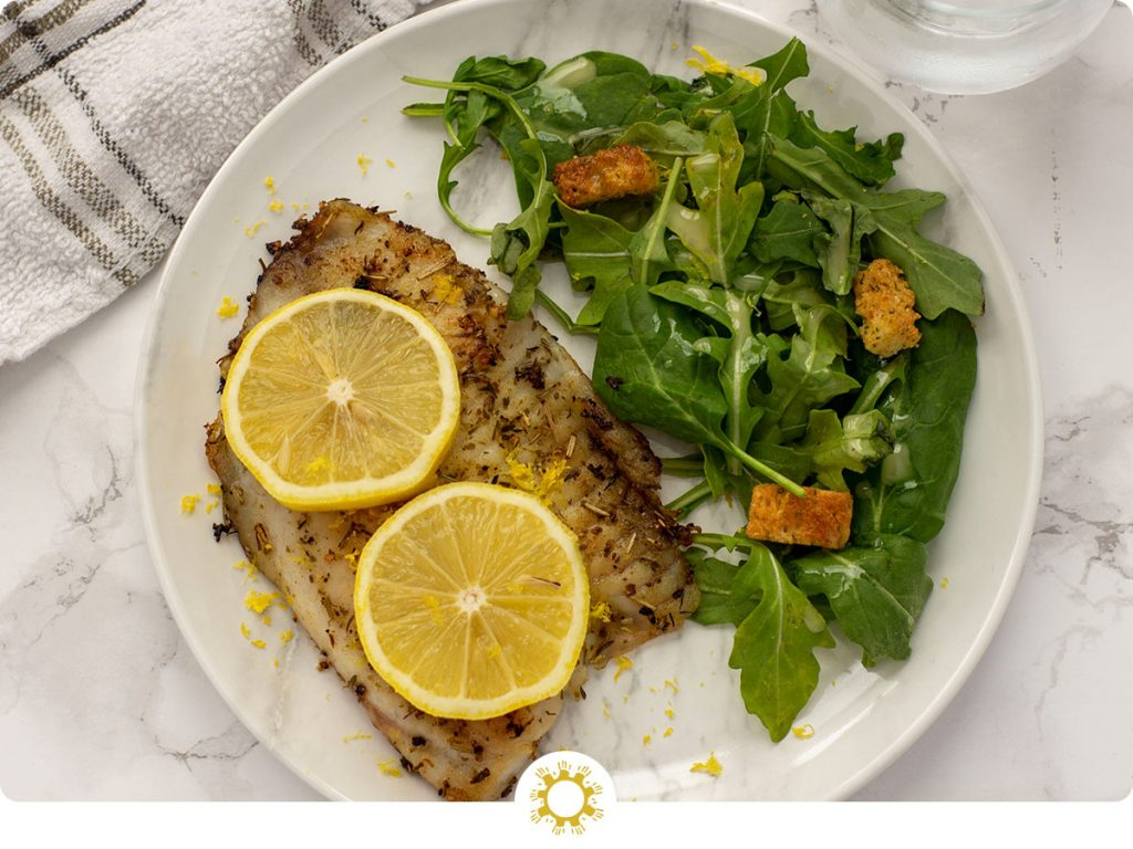 Top-down view of Lemon Rosemary Tilapia on a marbled plate with salad beside it on a grey marbled surface with a towel and glass of water (with logo overlay)