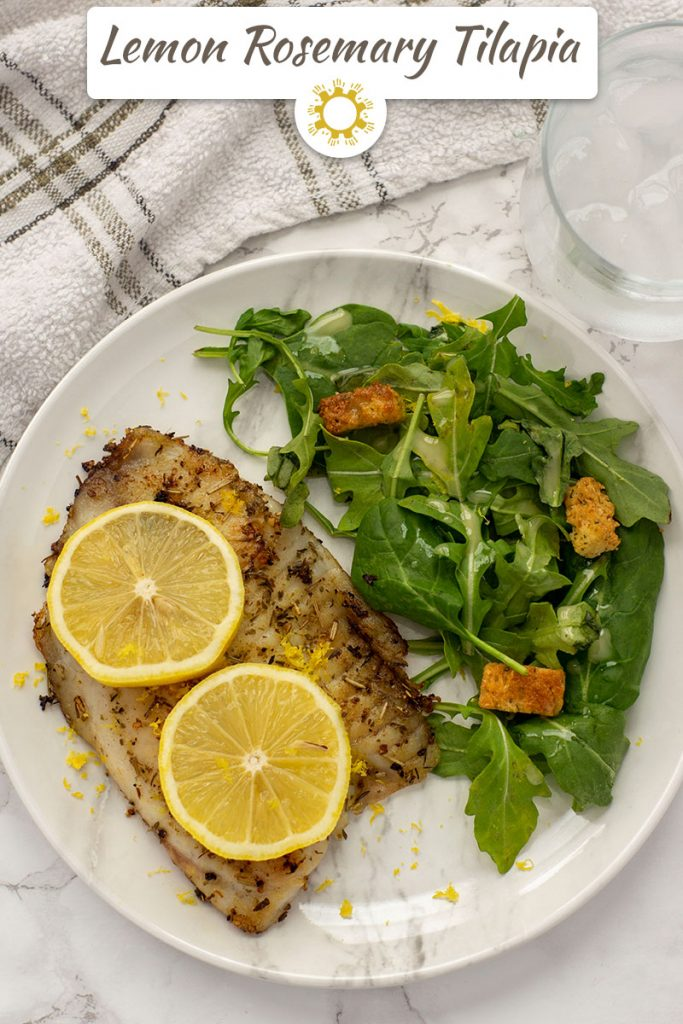 Top-down view of Lemon Rosemary Tilapia on a marbled plate with salad beside it on a grey marbled surface with a towel and glass of water (with title overlay)