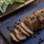 Marinated Baked Pork on a dark granite platter on a wooden surface with a salad in the background on a brown plate (with title overlay)