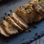 Marinated Baked Pork on a dark granite platter on a wooden surface