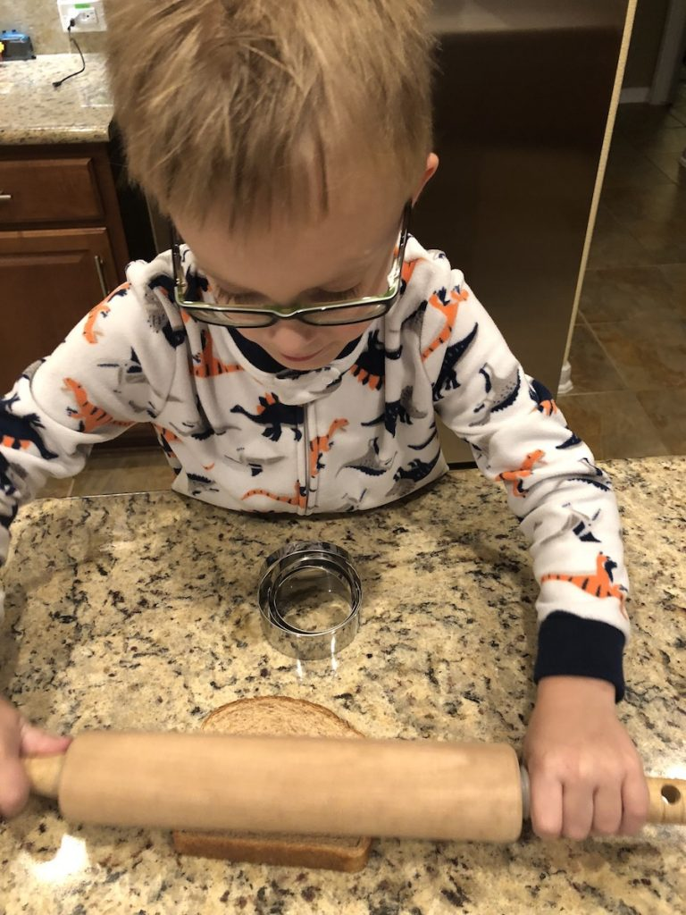 Young boy in pajamas using a wooden rolling pin to flatten bread