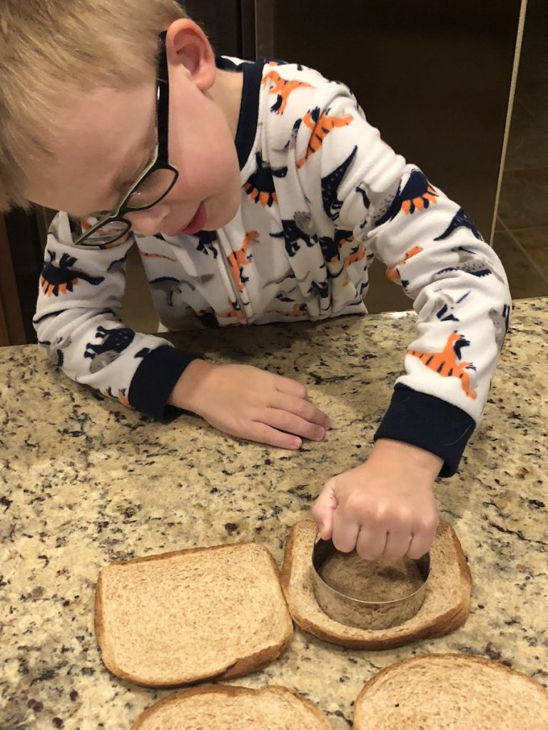 Young boy in pajamas using a round biscuit cutter to make circles in flattened bread on a granite countertop