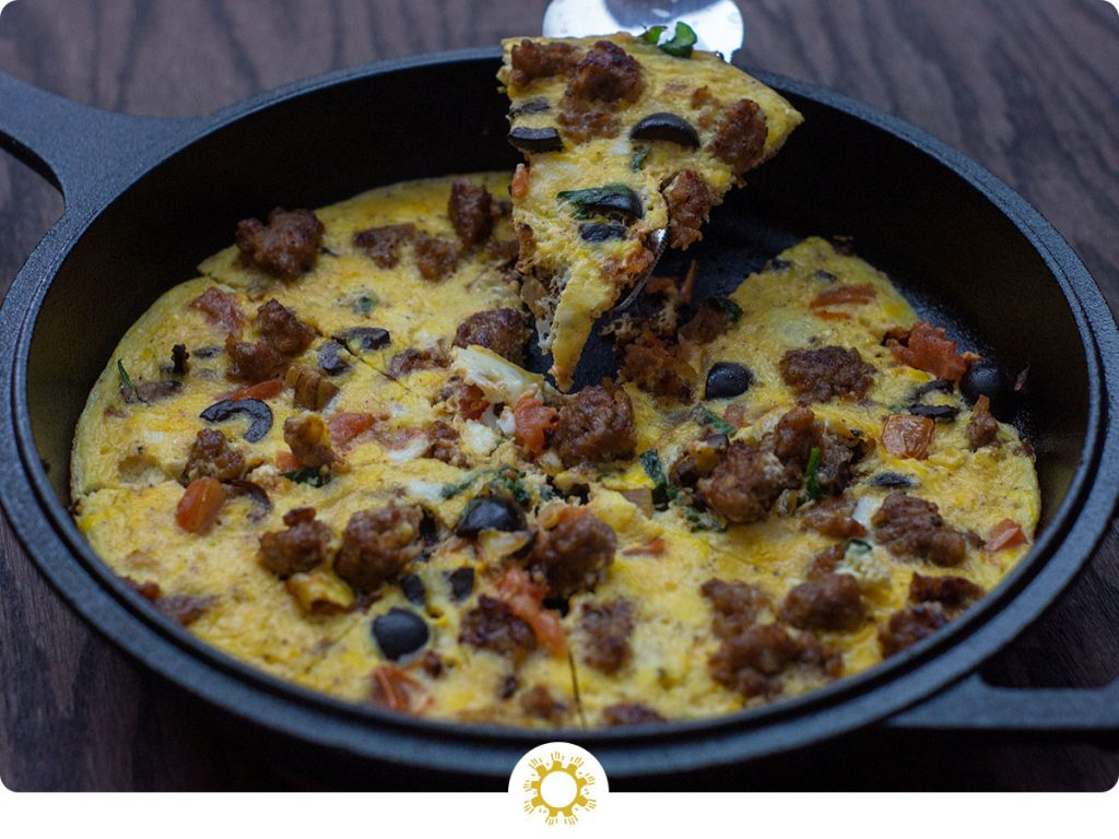 Sausage and Vegetable Frittata in a cast iron skillet with a slice being lifted on a triangle server (with logo overlay)