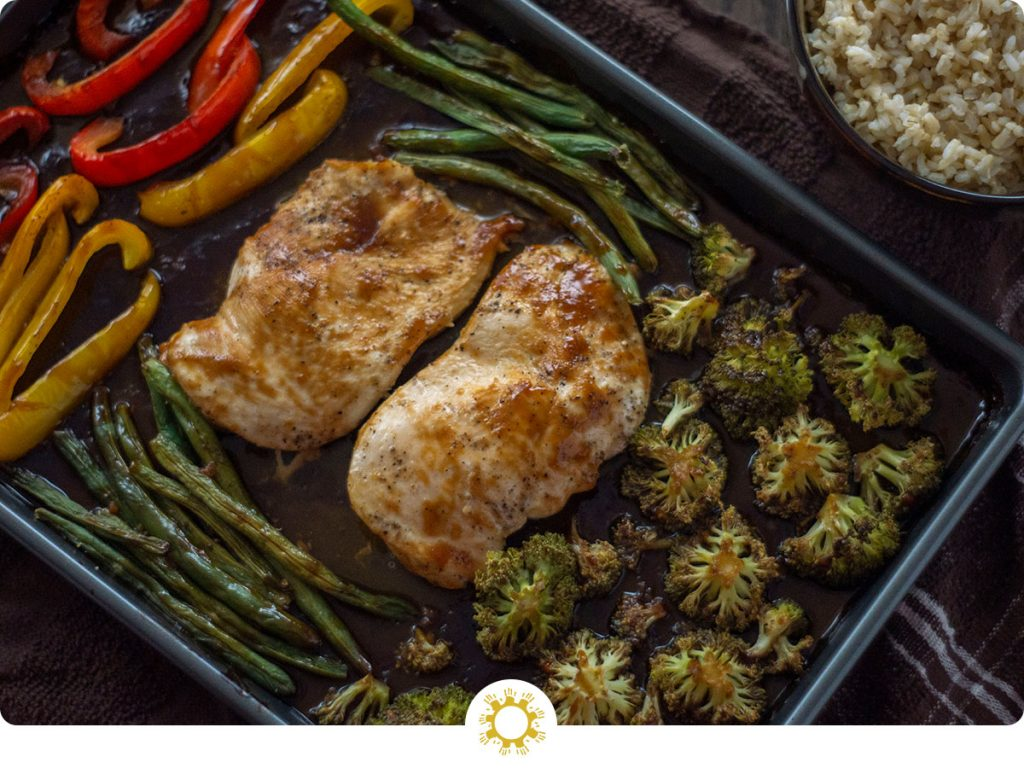 Quick and Easy Teriyaki Chicken Bake on a wooden surface next to a bowl of rice (with logo overlay)
