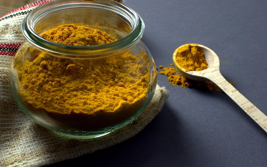Ground turmeric in a glass jar next to a wooden spoon with turmeric