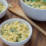 Cheesy Spinach Orzo Pasta Sides in a small white bowl next to a wooden spoon with two more bowls in the background all on a wooden surface (vertical with title overlay)