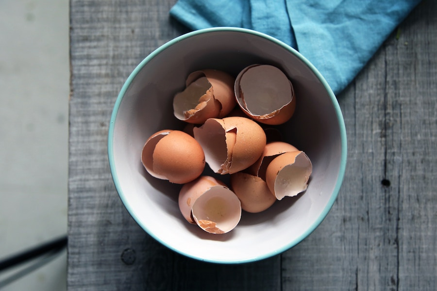 Egg shells in a bowl next to a blue napkin on a grey surface