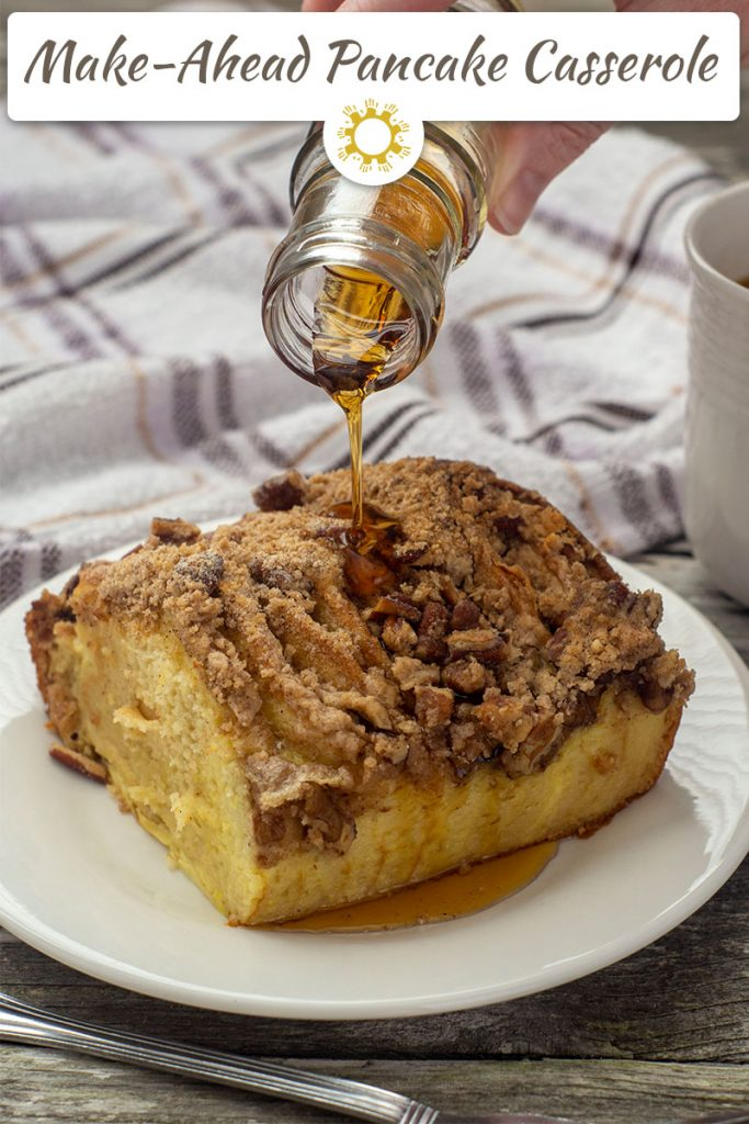 Piece of baked pancake casserole on a round white plate with maple syrup being poured on top next to a fork with a towel and cup of coffee behind all on a wooden surface (vertical with logo overlay)