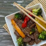 Top-down of Mongolian Beef Stir-Fry in a square white bowl with chop sticks on a wooden surface with a bamboo placemat (with title overlay)