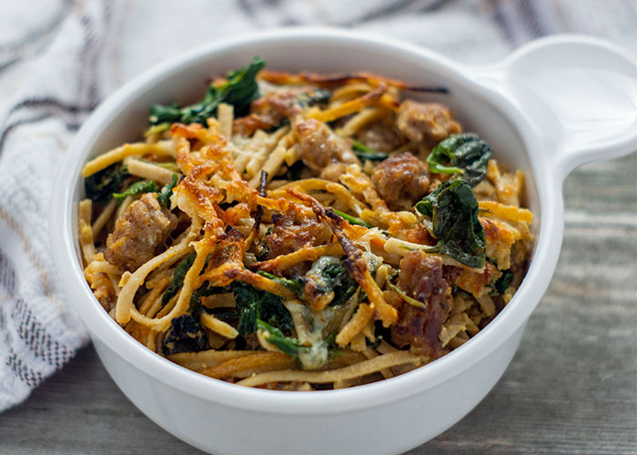 Sausage and Spinach Spaghetti Pie in a round white bowl next to a white and brown towel on a wooden surface