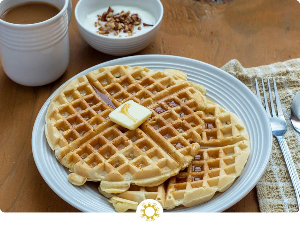 Two waffles with a pat of butter and syrup on top on a white plate next to a tan napkin with a fork and a cup of coffee and a yogurt parfait in the background on a wooden surface (with logo overlay)