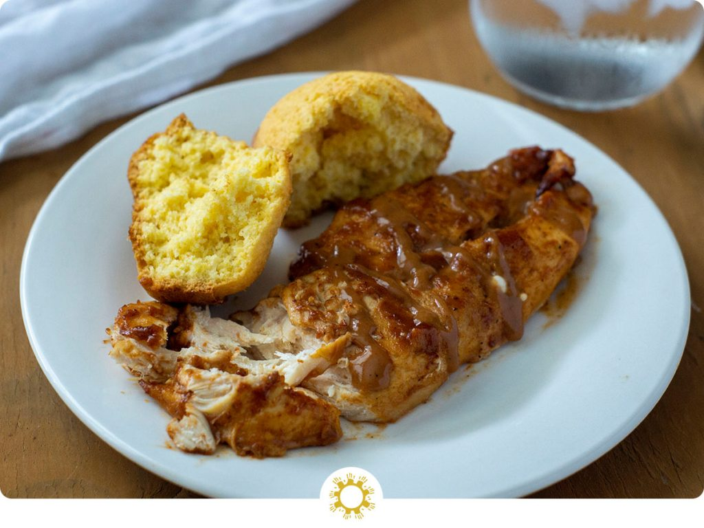 BBQ ranch chicken on a white plate with cornbread (with logo overlay)
