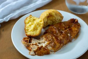 BBQ ranch chicken on a white plate with cornbread
