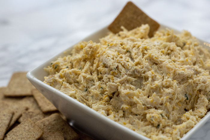 Cheesy Ranch Chicken Dip in a square white bowl next to a pile of square crackers on a white and grey marble surface